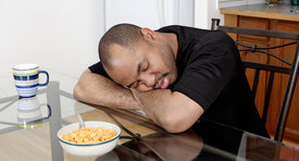 Man asleep at his breakfast table