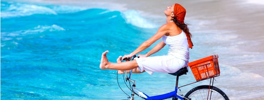Woman cycling on the beach